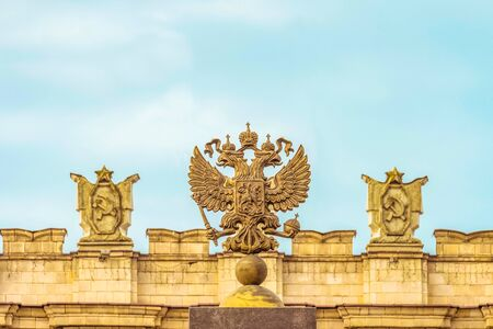 Coat of arms Russian Federation. Coat of arms  on the background of the parapet of the administrative government building with Soviet symbols. Stock Photo