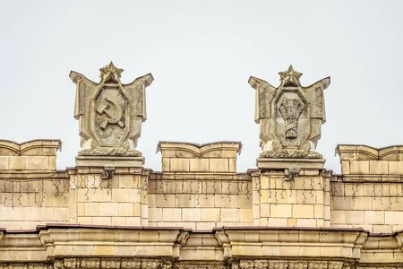 dictatorial: Fragment of parapet administrative government building with USSR symbols . Posters with the hammer and sickle, spikelets bunch. Ornament of the Stalinist Empire style of architecture.
