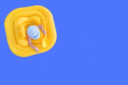 Baby floats in a yellow inflatable raft. Small child with a shovel in yellow rubber ring on a blue background with copy space. View from the top.