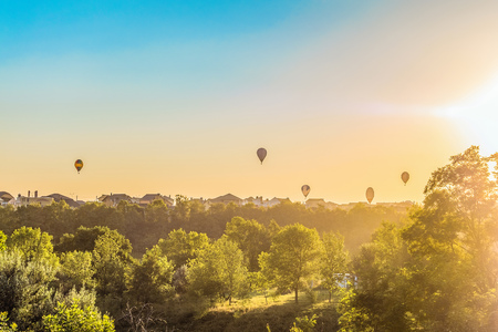Hot air balloons over the roofs of suburban houses in the light of the low evening sun backlight. Landscape with flying aeroststs on the horizon. Belgorod region, Russia.