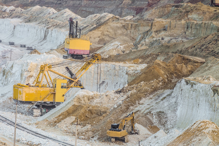 Work of heavy mining excavators in the chalky quarry. Heavy chalk mining industry.