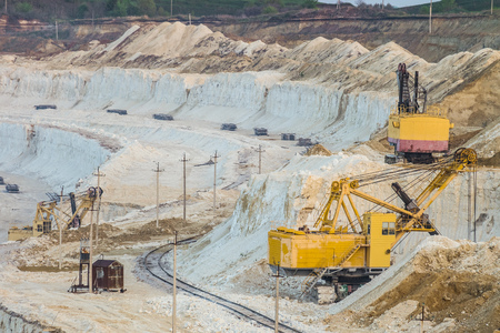 scarp: Mining excavators in the chalky quarry. Heavy chalk mining industry.