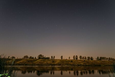 hillside: Starry night over the lake. Night landscape. Stock Photo