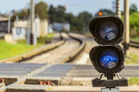 Semáforo de enrutamiento con una señal roja en el ferrocarril. Cruce de ferrocarril con semáforo. Profundidad de campo limitada. Foto de archivo