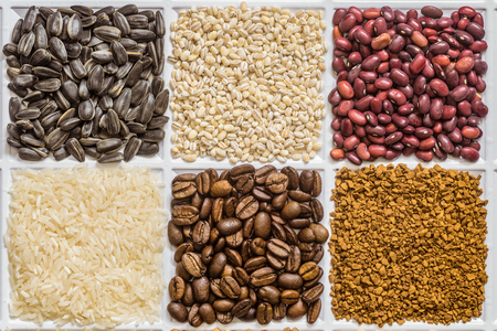 Grocery set of food products: sunflower seeds, pearl barley, dried seeds of red beans, rice, roasted coffee beans, freeze-dried instant coffee. Stock Photo