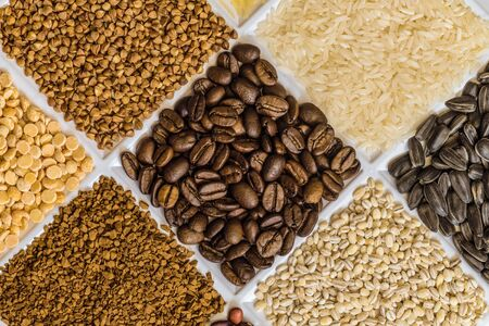 Roasted coffee beans in set of groceries with buckwheat, rice, sunflower seeds, pearl barley, freeze-dried instant coffee, dried peas. Stock Photo