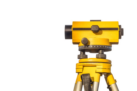 Geodetic optical level isolated on a white background. Construction engineering equipment with copy space.
