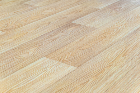Linoleum flooring with embossed light wood texture close-up. Horizontal layout perspective. Limited depth of field.
