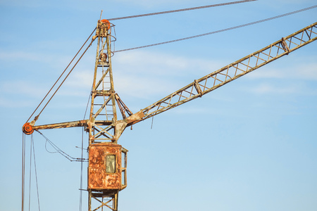 Cabin of old abandoned rusty tower crane on a blue sky background