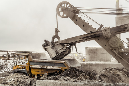 Bucket excavator loads into a large mining dump truck. Heavy industry. Stock Photo