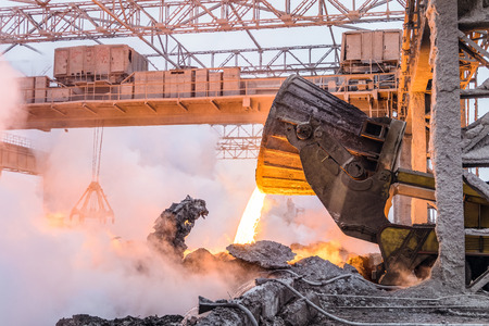 crucible: Pouring the red-hot melt by truck transporter with ladle. Metallurgical work in heavy industry.