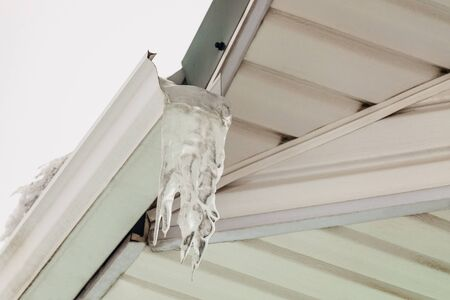 Fragment of roof overhang with icy icicle gutter after thaw.