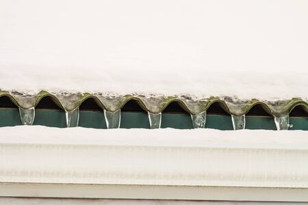 Snow-covered icy roof overhang with gutter after thaw. Frozen drain.