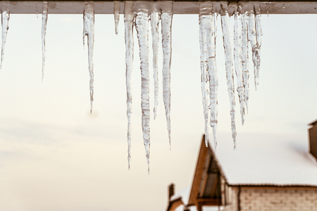 Icicles on the edge of roof overhang. Winter thaw. 版權商用圖片 - 87794430