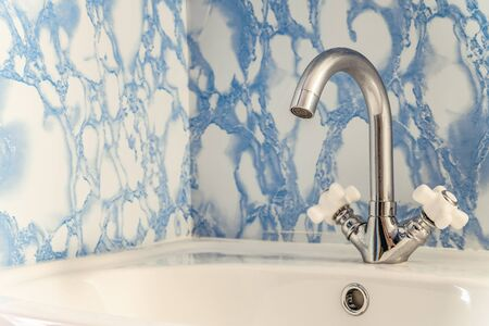 Chromed washbasin with white sink and two valves