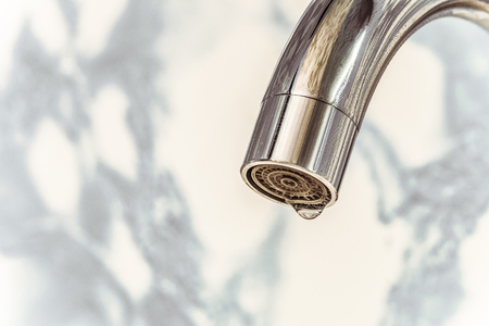 Chromed spout of a water tap with a drop on the aerator. Close-up.