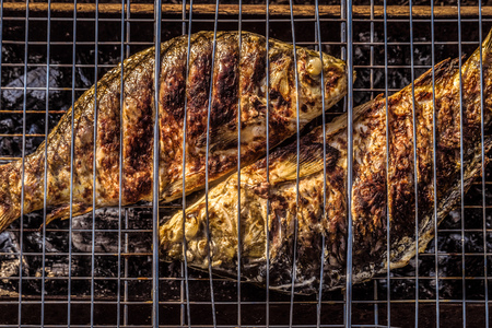 Baked on charcoal grill fish. Cooked carp.