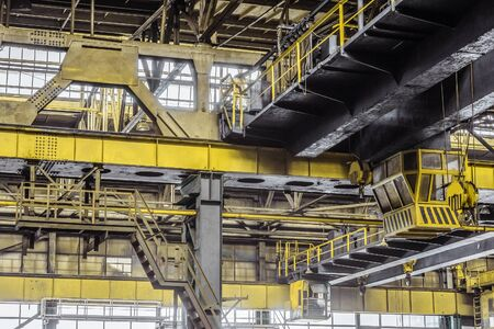 Overhead cranes with a crane operator cabin and hooks in a multi-span metal frame workshop. Steel landing pad. Stok Fotoğraf
