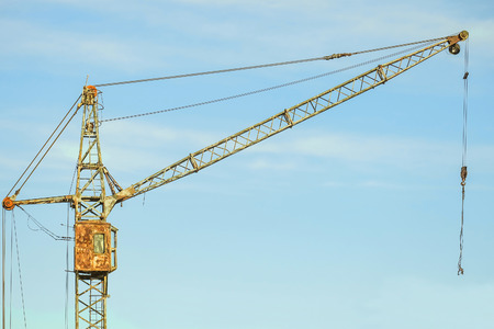 Old abandoned rusty tower crane on a blue sky background