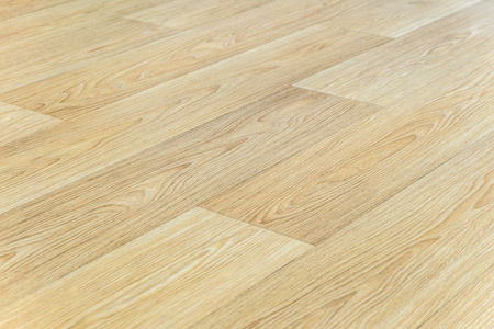 Linoleum flooring with embossed bright beige wood texture. Background with limited depth of field.