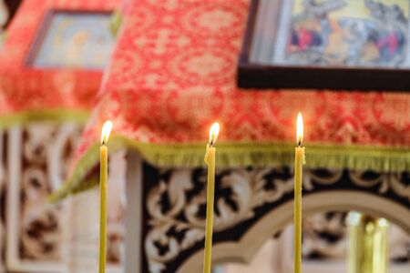 Three burning candles on a blurred background of the pulpit with an icon for liturgy, prayers and sermons. Russian Orthodox Church. Selective focus. Stock Photo