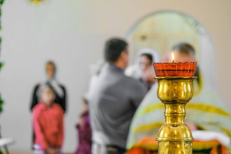 Church floor candlestick with a burning candle close-up. Kandilo in the Orthodox Christian church. Background with selective focus. Stock Photo