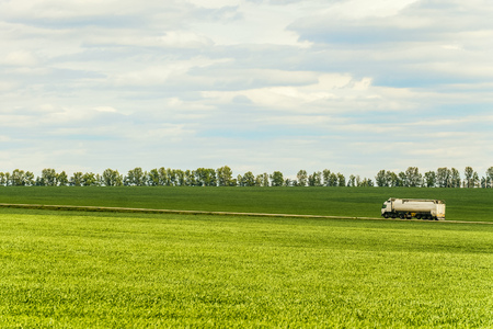 Green landscape with white tank trailer truck driving along a country road amidst farming fields