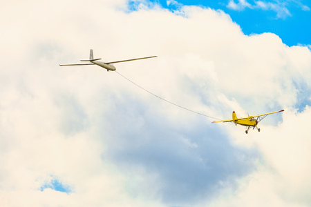 Yellow small light-engine sport plane flying in the cloudy sky pulls on a rope the glider plane Stock Photo