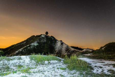 Starry night sky over the high chalk hill. Night natural landscape. Natural archaeological monument - Krapivenskoye ancient settlement, Belgorod region, Russia. Stock Photo