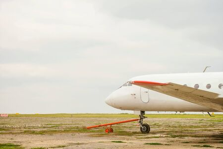 Old white passenger plane with a cruel hitch for transportation, standing in the parking lot Фото со стока