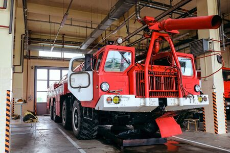 Large four-axle airfield fire truck standing in the garage of the fire box