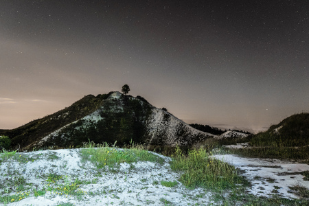 Dark night sky over the high chalk hill. Night natural landscape. Belgorod region, Russia.