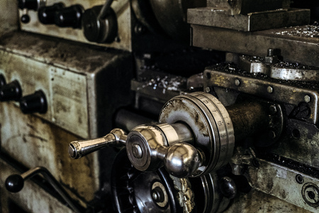 Detail of old lathe. Handle with scale. Panel of controls the classic broom lathe. Metalworking.
