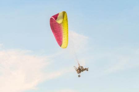 Take-off of the motor paraglider trike skyward. Flight on motor glider in the blue sky.