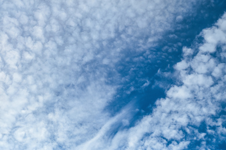 Beautiful clouds on a dark blue sky. Heavenly background. Universal template for background insertion.