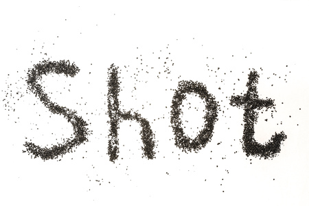 Steel shot for blasting machine. Inscription SHOT on a white surface with scattered small metal granules. Stock Photo