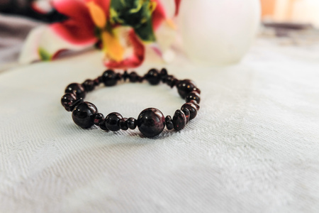 Handmade bracelet of garnet stones on a fabric surface with limited depth of field. Blurred background. Stock Photo