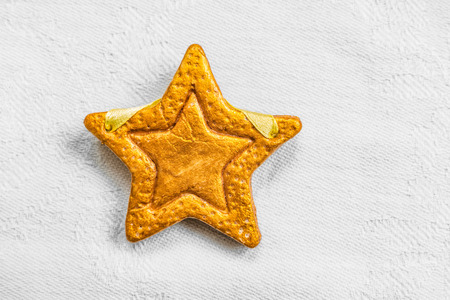 Decorative golden star handmade from dough on a bright white fabric surface. View of the top. Stock Photo