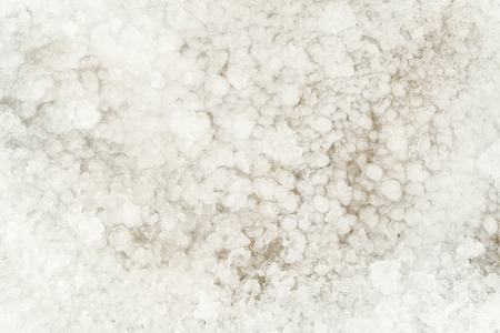 Natural background of bright thawed snow. Frozen snow texture.