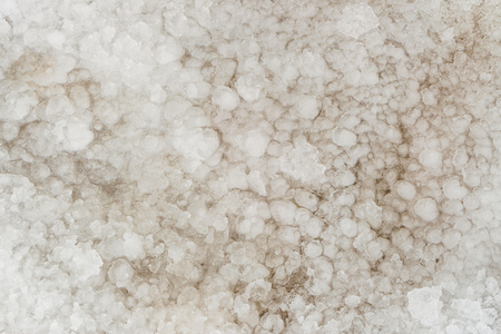 Natural background of thawed snow. Frozen snow texture.