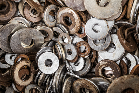 Metal washers in set. Spent fasteners background.
