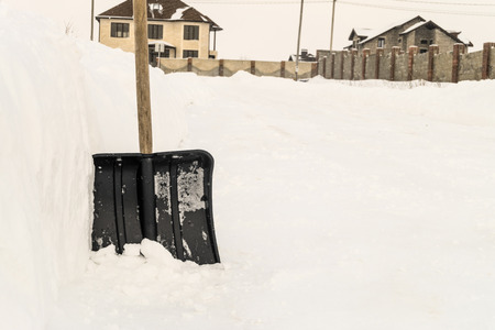 Snow shovel near a snowdrift by the road in a low-rise suburban residential area. Shovel for cleaning the footpaths from snow.