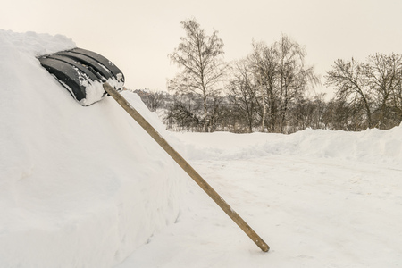 Snow shovel on a high snowdrift near countryside road. Shovel for cleaning the footpaths from snow. Stock Photo
