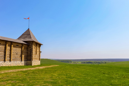 Wooden fortress with tower and flagstaff on a green meadow at plain