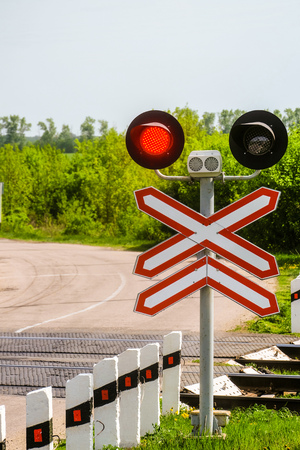 Railway traffic lights with a red signal. Railway and road crossing. Forbidding Motion signal. Banque d'images