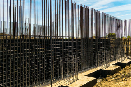 Reinforcing cage with joining longitudinal and transverse reinforcement. Shielded steel formwork for the construction of reinforced concrete monolithic structures. Stock Photo