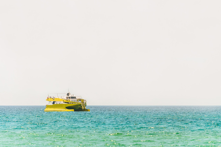 Yellow pleasure boat at turquoise waters of the sea horizon Stockfoto