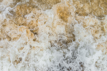 Raging sea surf close-up. Abstract background. Sea foam on the sandy shore.