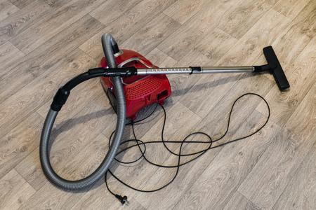 Red vacuum cleaner with electric cable laid out on the linoleum floor