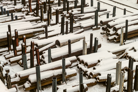 Outdoors industrial warehouse of finished steel pipes and metal products. Storage site at winter time. 版權商用圖片